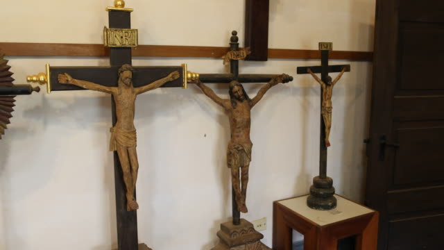 A pan to the left showing wooden crucifixes presented at the Mission Museum in Concepción
