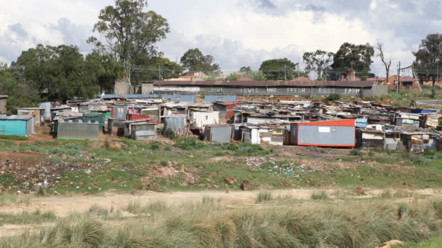 a pan to the right showing a slum next to orlando stadium in soweto a township of johannesburg - soweto stock videos & royalty-free footage