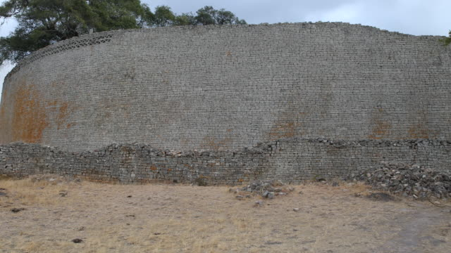 pan to the right, showing the exterior wall of the great enclosure of an ancient city complex in the south-eastern hills of zimbabwe, which used to... - enclosure stock videos & royalty-free footage