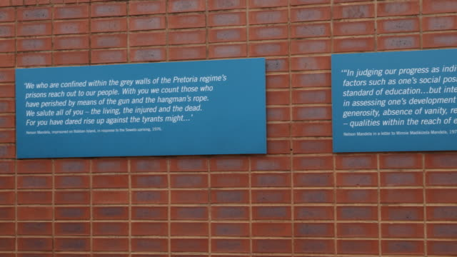 pan to the right, showing two blue signs with inscriptions on a red brick wall with quotes of nelson mandela. - biographie stock-videos und b-roll-filmmaterial