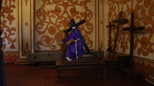 a pan to the right showing wooden crosses and a wooden figure of jesus carrying a cross placed on a short table inside of the mission church the... - jesuit stock videos and b-roll footage