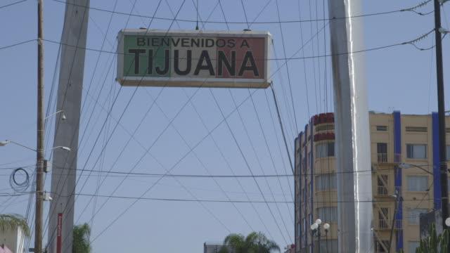 pan to tijuana welcome sign, medium shot - tijuana stock videos & royalty-free footage