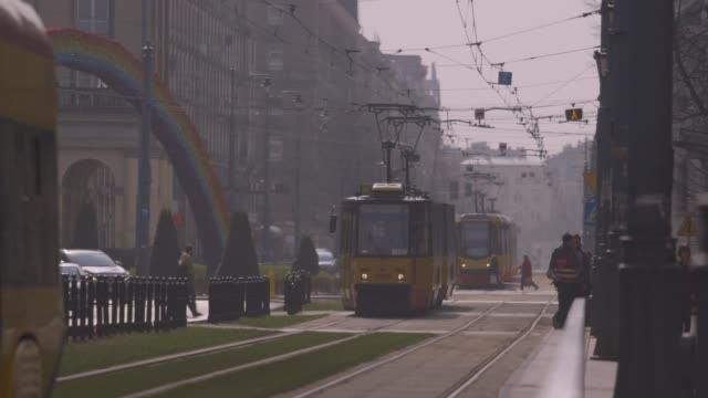 pan to trams and large rainbow-coloured arch in warsaw - warsaw stock videos & royalty-free footage