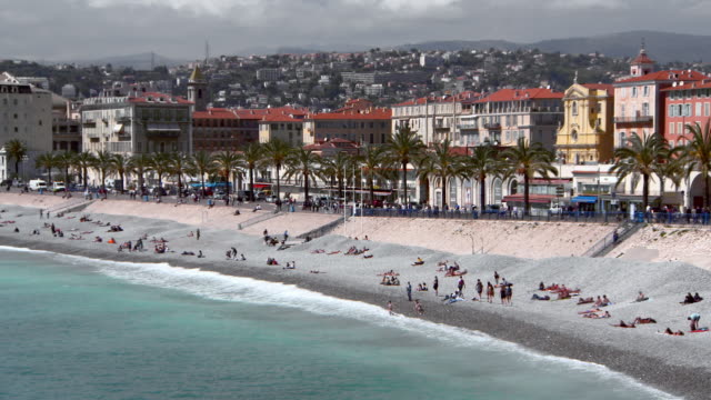 pan: tourists sunbathe on the beach at nice - region provence alpes côte d'azur stock-videos und b-roll-filmmaterial