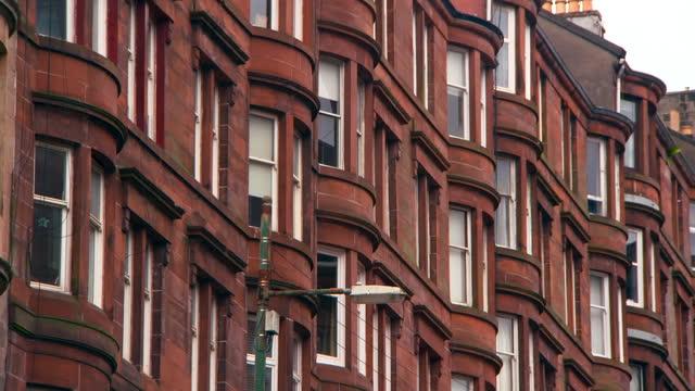 pan: towering red sandstone georgian tenement building with white trimmed windows - glasgow, scotland - ジョージア調点の映像素材/bロール