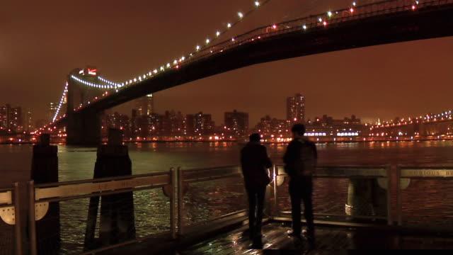 tl ws pan two people standing on pier under brooklyn bridge at night/ new york city - ブルックリン橋点の映像素材/bロール