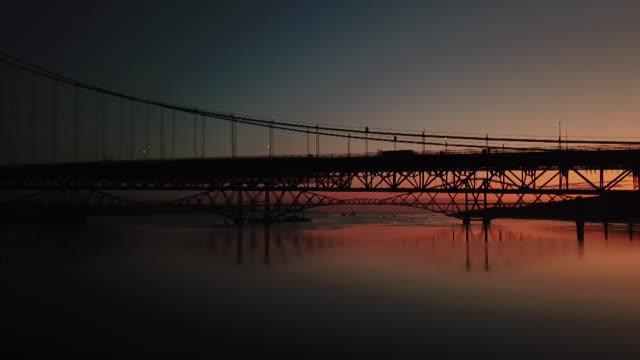 pan under forth bridge at sunrise - fluss firth of forth stock-videos und b-roll-filmmaterial