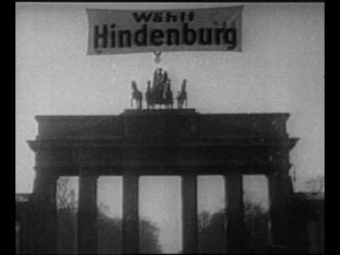 pan up 1932 campaign poster for adolf hitler for german president / hitler rides through saluting crowd in open automobile / campaign banner for... - adolf hitler stock-videos und b-roll-filmmaterial