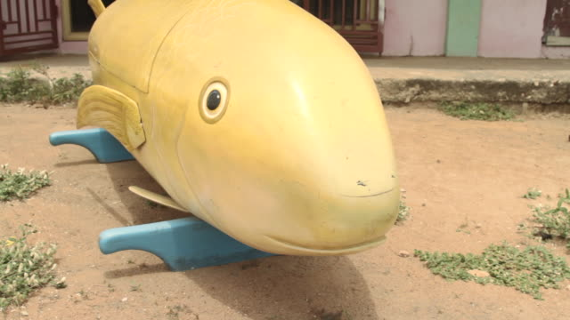 pan up a coffin styled in the shape of a fish in the city of accra. - 棺点の映像素材/bロール