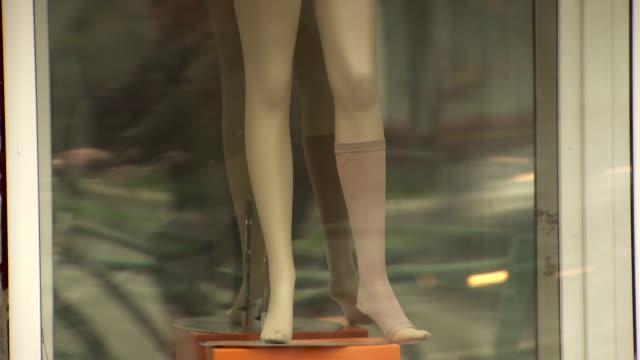 Pan up a mannequin in a shop window modelling underwear.