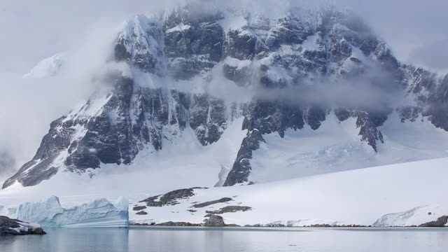 Pan up a mountain in Antarctica, partially in clouds