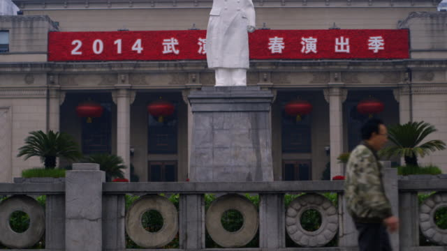 Pan up a statue of Chairman Mao in the city of Wuhan.