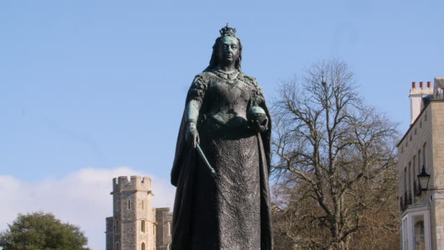 Pan up a statue of Queen Victoria positioned next to Windsor Castle.