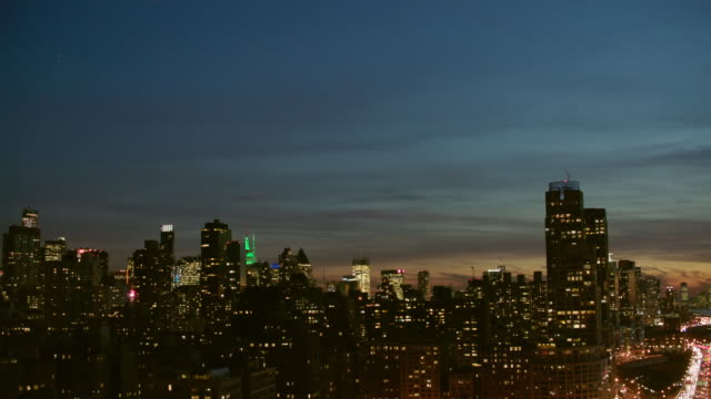 pan up aerial from West Side Highway to view of midtown Manhattan with lights on, NYC
