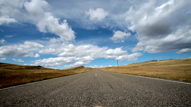 vídeos y material grabado en eventos de stock de pan up and down low wide angle view of empty paved road with puffy clouds and blue sky with shadows rolling across landscape. - carretera vacía