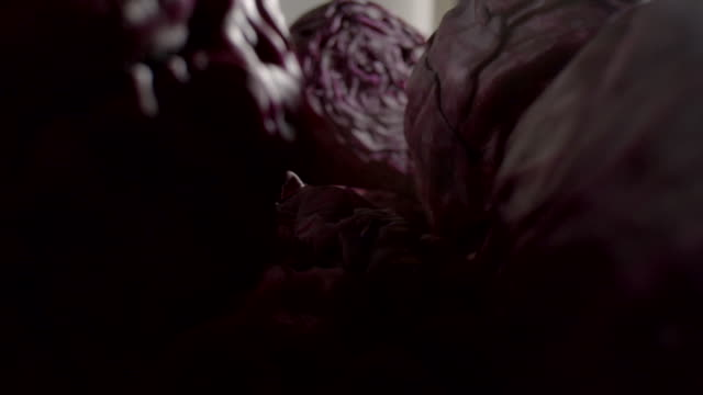 Pan up and down over a pile of red cabbages.