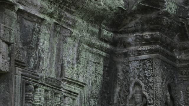 Pan up beautiful stone carvings adorning the walls at the Bayon temple in Angkor, Cambodia.