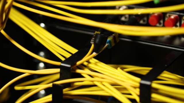 vídeos de stock e filmes b-roll de pan up bright yellow cables connected to a computer server. - complexidade