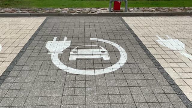 vídeos y material grabado en eventos de stock de pan up: electric car charging lot sign on pavement at parking lot - coche eléctrico coche alternativo