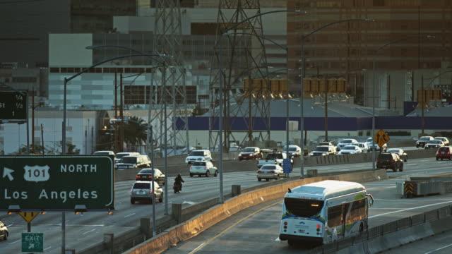 pan up la freeway interchange and downtown office buildings - motorway stock videos & royalty-free footage