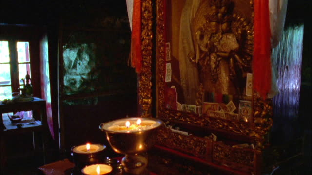pan up from candles flickering in bowl to buddhist shrine available in hd. - shrine stock videos & royalty-free footage