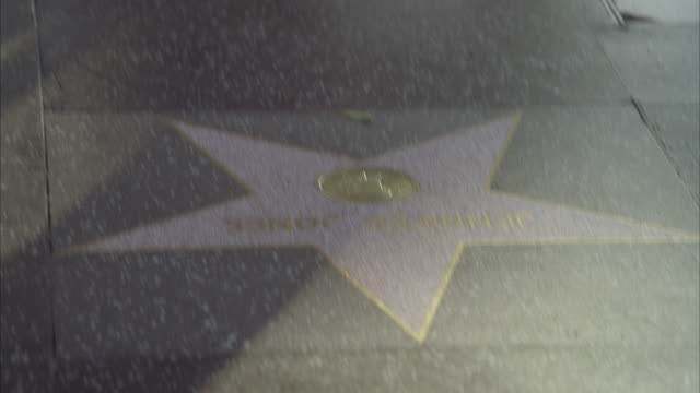 Pan up from hollywood walk of fame star to people or pedestrians walking. hollywood boulevard. los angeles area. landmarks.
