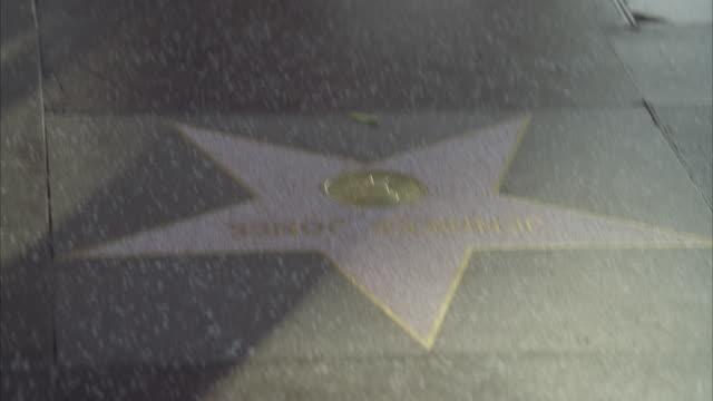 stockvideo's en b-roll-footage met pan up from hollywood walk of fame star to people or pedestrians walking. hollywood boulevard. los angeles area. landmarks. - hollywood walk of fame