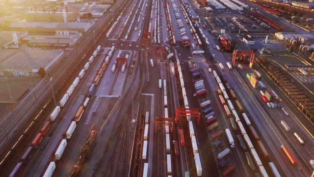 pan up from intermodal rail yard to downtown la skyline - aerial - cargo train stock videos & royalty-free footage