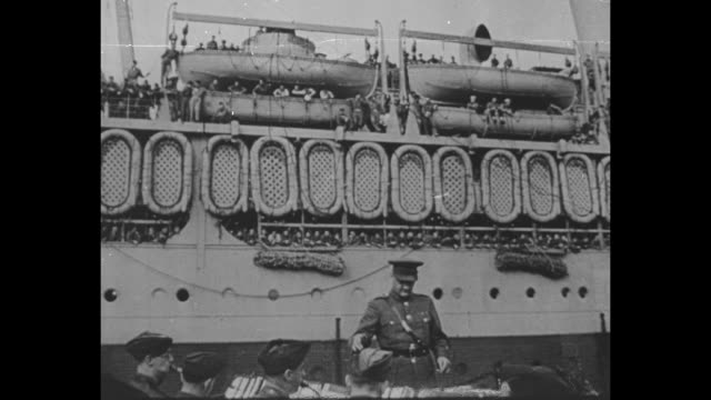stockvideo's en b-roll-footage met pan up from military band playing and conductor to ship with sailors at railings rafts hanging along ship and lifeboats hanging above them / closer... - d day