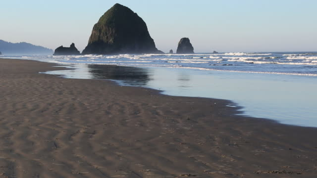 pan up from receding tide beach past waves to distant rock islands - receding tide stock videos & royalty-free footage