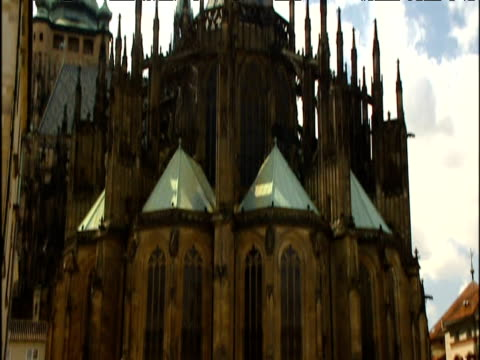 Pan up from street to spires of St. Vitus's cathedral in Prague.