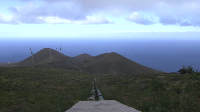 pan up from water pipes leading to a wind farm on the island of el hierro. - water pipe stock videos and b-roll footage