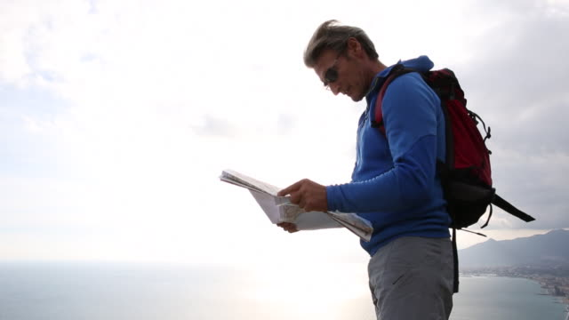 Pan up, hiker looks at map on cliff above sea