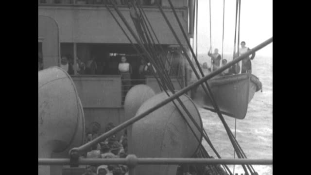 pan up mast of ship carrying survivors of the torpedoed wwi transport ship uss president lincoln / crew members conduct lifeboat drill / pan group... - 潜水艦点の映像素材/bロール