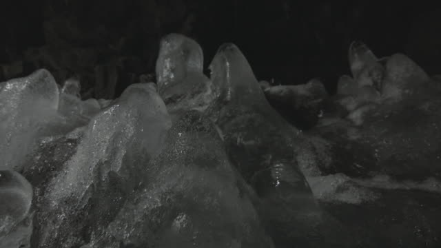 Pan up mounds of ice that have formed in a cave.