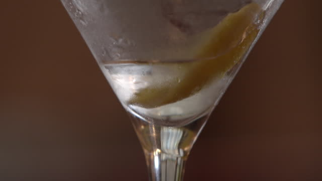 Pan up of a filled cocktail glass that is picked up and put down