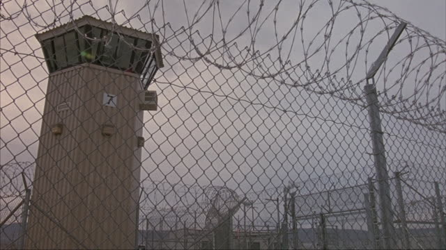 pan up of chain link fence with barbed wire on top. camera moves over fence, see guard tower to left, and prison yard in backyard. group of people standing by entrance of prison. - パン効果点の映像素材/bロール