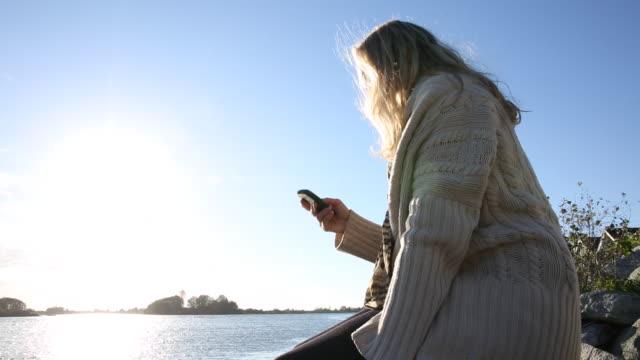 vídeos de stock, filmes e b-roll de pan up of mature woman taking photo with smart phone on river bank - smart