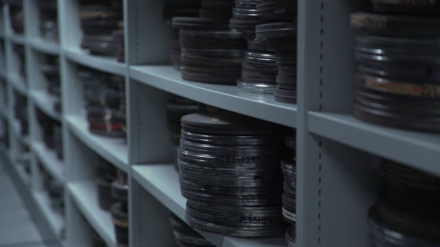 stockvideo's en b-roll-footage met pan up of metal film cans on a shelving unit - bbc archives