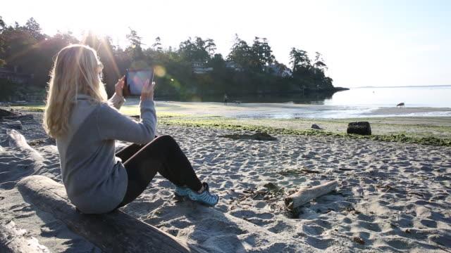 pan up of woman using digital tablet, relaxes on beach at sunrise - カナダ ビクトリア市点の映像素材/bロール