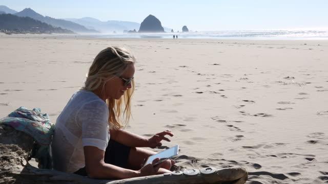 pan up of woman working on digital tablet on beach, medium shot - オレゴン沿岸点の映像素材/bロール