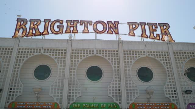 pan up the exterior of the amusement arcade on brighton's palace pier. - ブライトン パレスピア点の映像素材/bロール