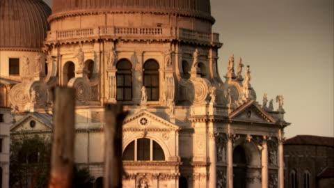 pan up the exterior of the santa maria della salute in venice. - bird video stock e b–roll