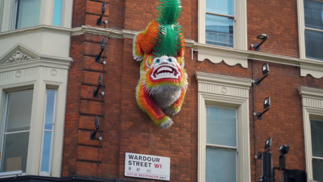 Pan up to a decorative Chinese lion hanging from a building on London's Wardour Street.