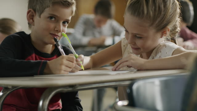 pan up to girl writing on paperwork of boy at desk in classroom / provo, utah, united states - provo stock videos & royalty-free footage