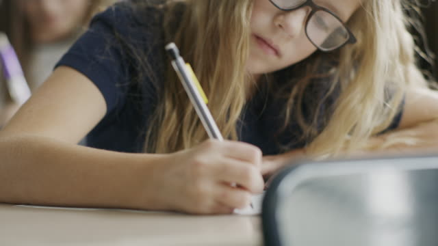 pan up to girl writing on test at desk in classroom / provo, utah, united states - educazione video stock e b–roll