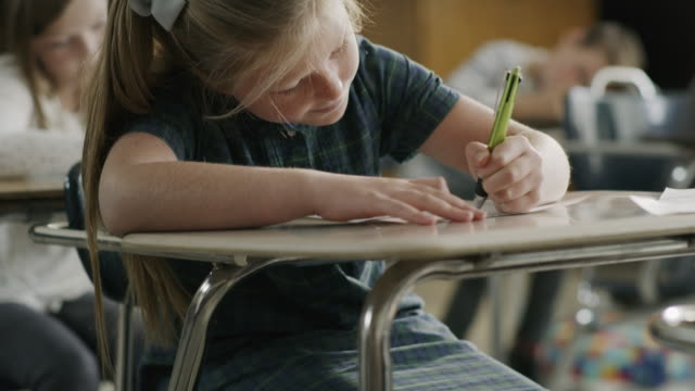 Pan up to girl writing on test at desk in classroom / Provo, Utah, United States