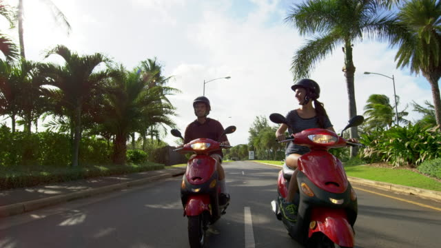 pan up to reveal a man and a woman riding mopeds together - moped stock videos and b-roll footage