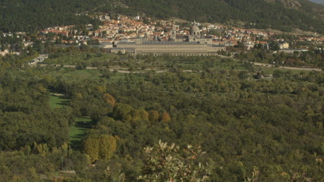 pan up to the town of san lorenzo de el escorial and the grand palace of el escorial, spain. - 宮殿点の映像素材/bロール