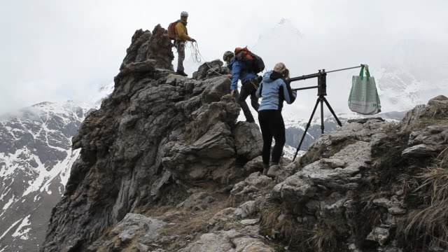 vídeos de stock e filmes b-roll de pan up to woman filming two mountaineers with snowy moutain in the background - marinheiro